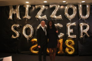 Student Taiwo Adeshigbin standing in front of balloons that spell out Mizzou Soccer 2018 with head coach Bryan Blitz