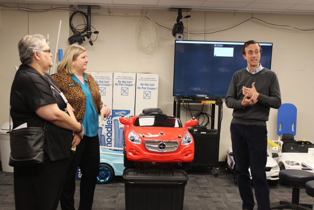 OT Professor Bill Janes explains the Go Baby Go! Program in front of car to two Extension employees.