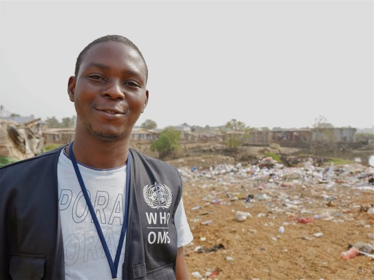 Ifeolu David stands in the foreground wearing a grey T-shirt under a black vest with the World Health Organization logo and acronyms WHO, OMS