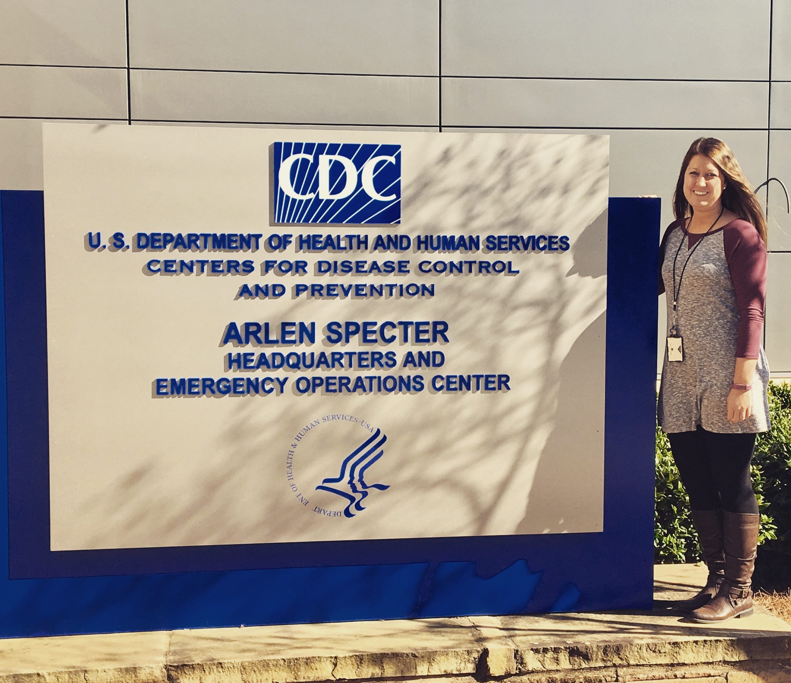 Marissa Thomas standing in front of the sign outside the CDC Washington office