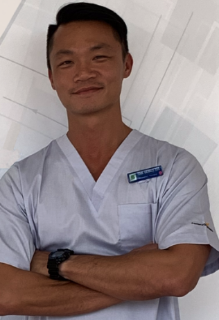 Ivan Lee, a respiratory therapist, standing in front of a white and grey back drop, wearing scrubs, with his arms crossed, in the hospital he works in