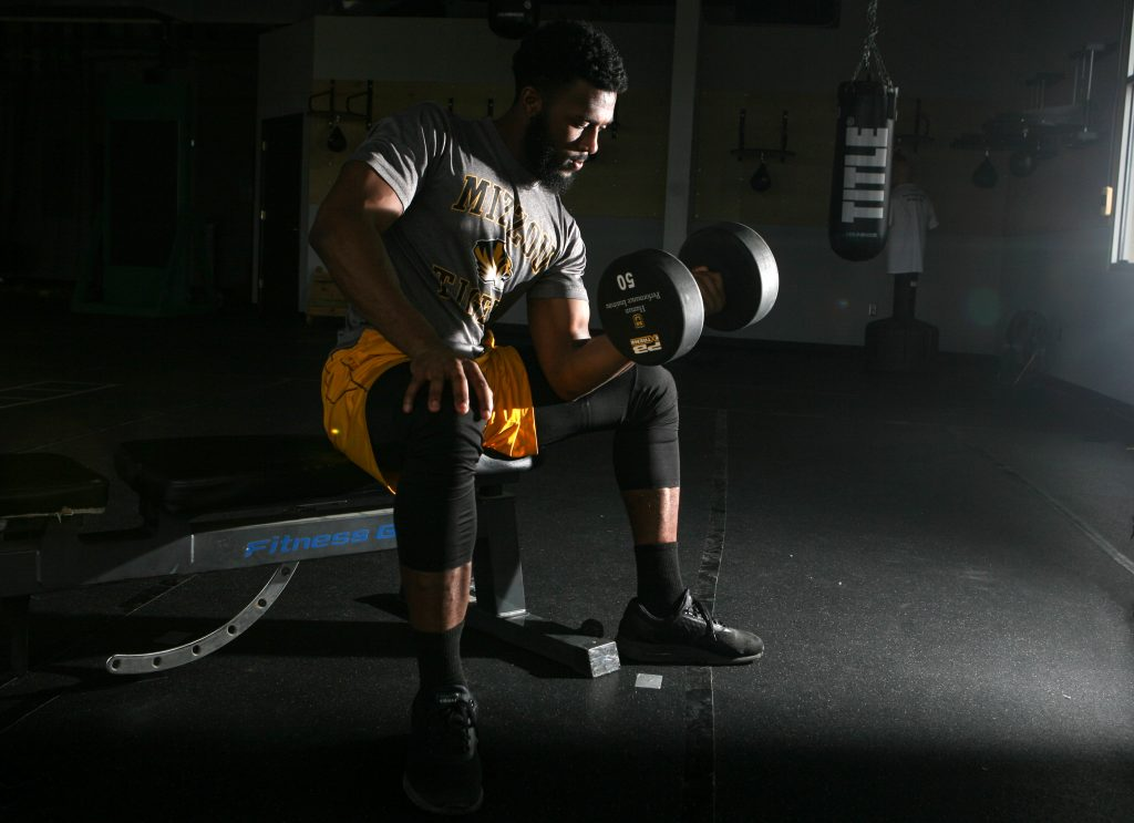 A man sits in a dramatically lit room lifting a large dumbell