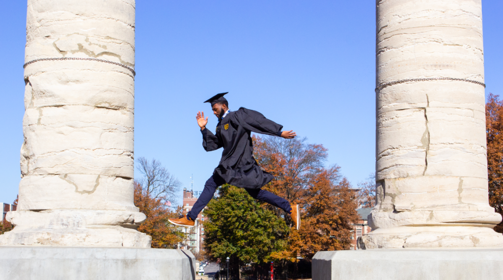 A black man in graduation cap and gown leaps from one large column to the other.