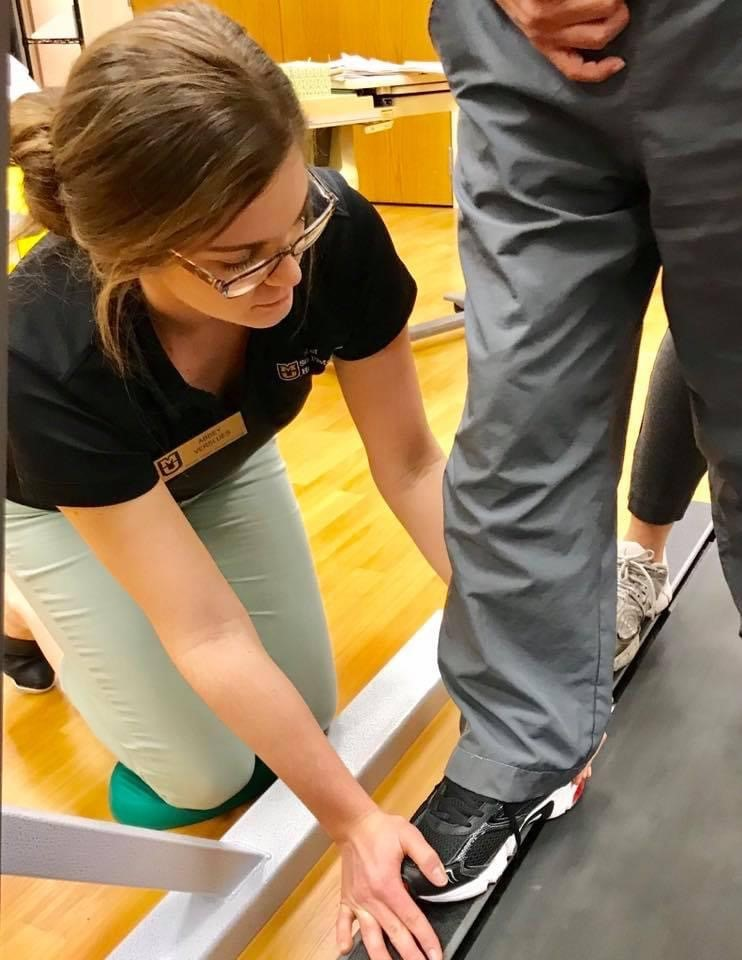 Abbey Twehous kneels next to a client's foot on a treadmill in the PhysZOU clinic