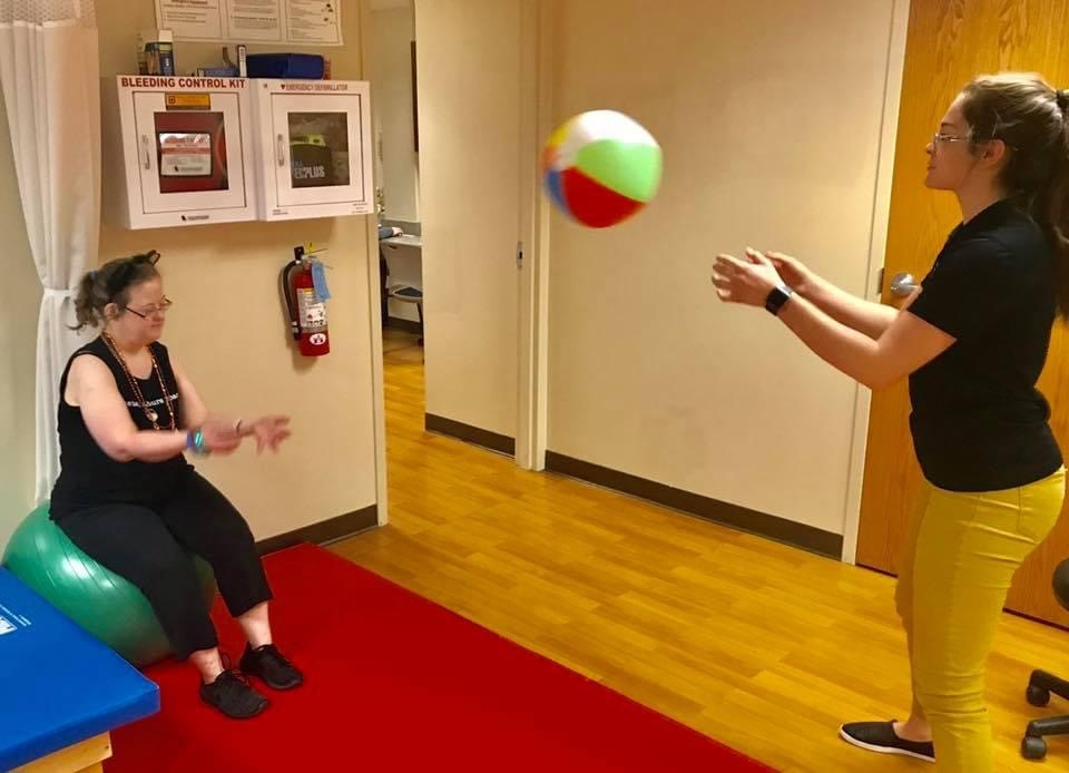 Abbey Twehous tosses a beach ball to a client in PhysZOU