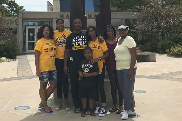 A Black family wearing black and gold t-shirts in front of a residence hall