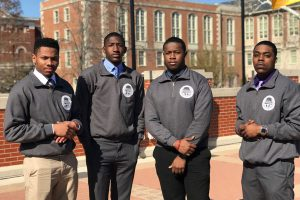 Four Black men with serious expressions wearing matching gray quarter-zip jackets