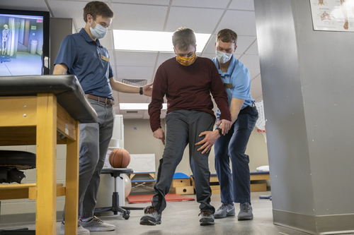 Physical therapy students help steady a man as he walks