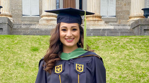 Woman with long brown hair wearing a graduation cap and gown