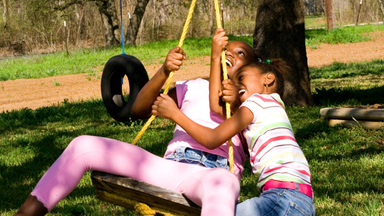 Two girls laughing on a tire swing
