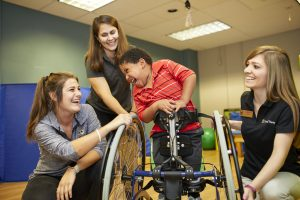 A boy in a wheelchair laughs with two physical therapy students and one instructorr