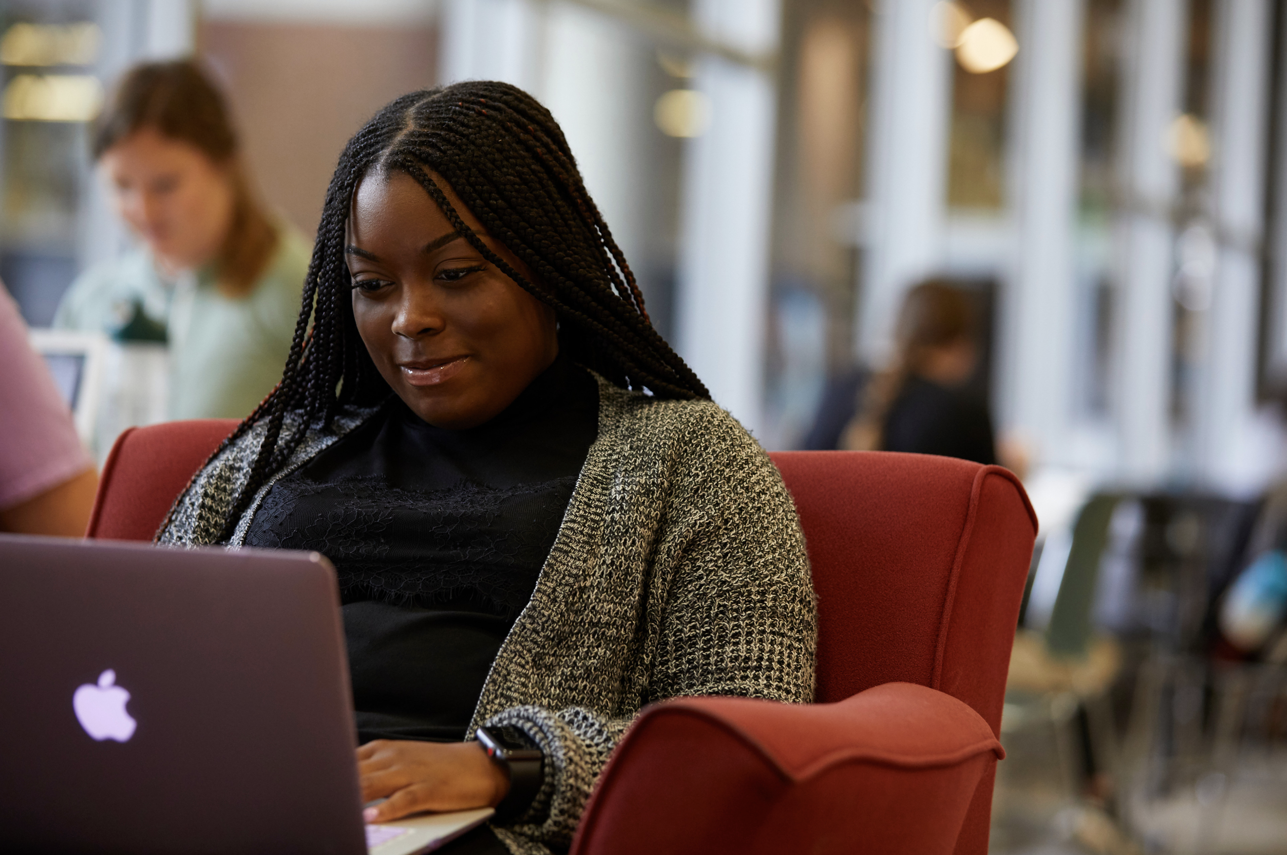 College student who identifies as female in Lewis/Clark lobby smiling at her laptop screen