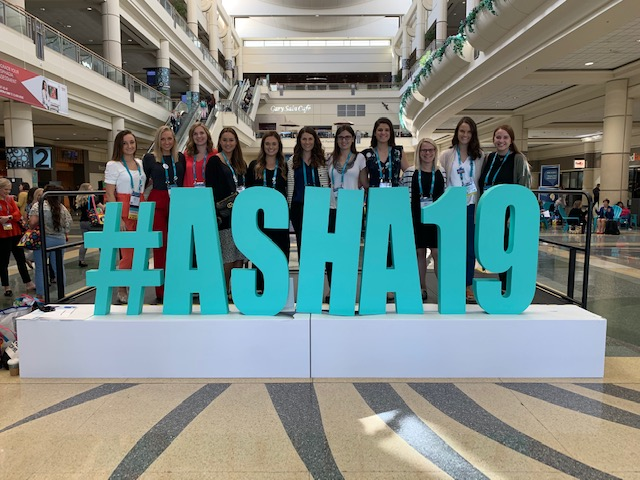 "Students stand behind a large teal sign that reads, ""#ASHA19"""